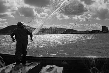 Homem em barco soltando rede pesca artesanal